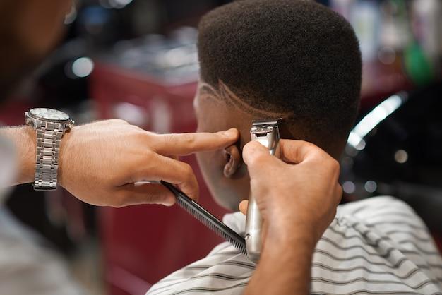 Gros plan de la coupe des rayures sur la tête masculine dans un salon de coiffure