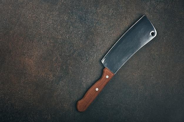 Gros plan d'un couperet à viande en métal de boucherie avec manche en bois sur la surface de la table de cuisine grunge, vue de dessus surélevée, directement au-dessus
