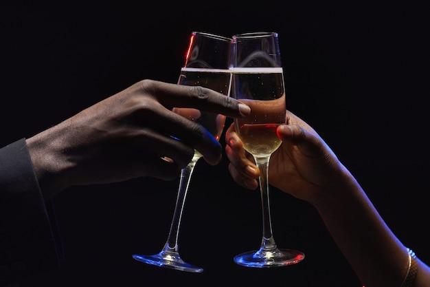 Gros plan d'un couple afro-américain méconnaissable tinter des verres de champagne dans l'obscurité, copiez l'espace