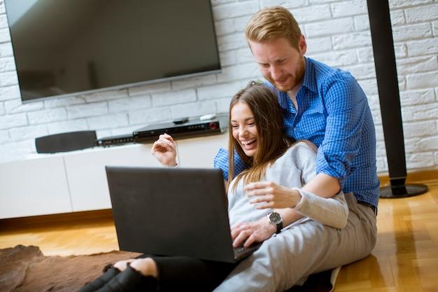 Gros plan d'un couple à l'aide d'un ordinateur portable assis sur le sol dans leur salon