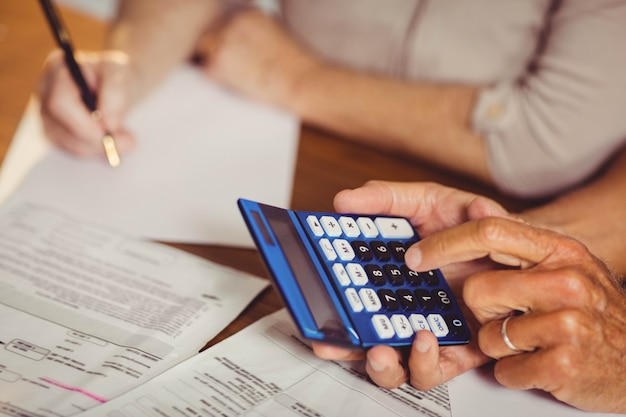 Gros plan, couple aîné, compter, factures, chez soi