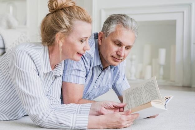 Gros plan, couple aîné, lecture livre