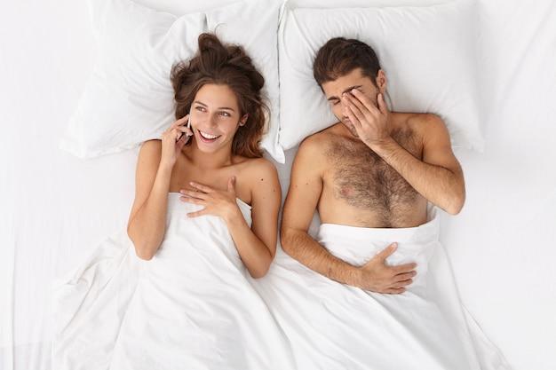 Gros plan sur couple allongé dans son lit sous une couverture blanche