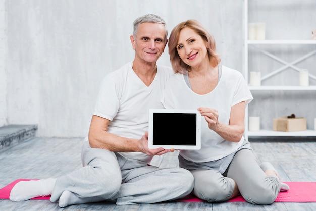 Gros plan d'un couple d'amoureux tenant une tablette numérique à écran noir