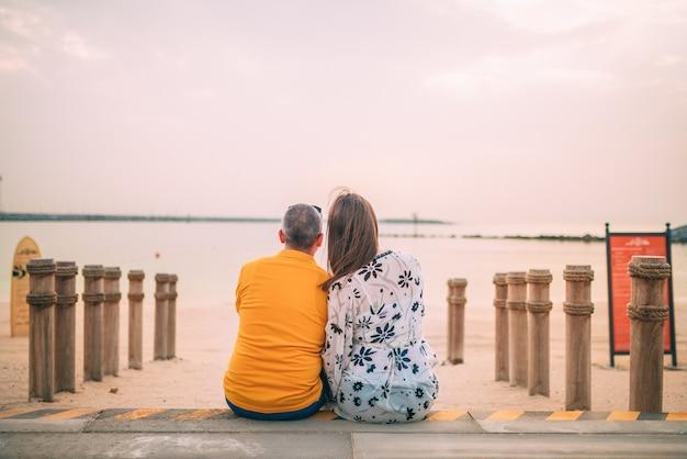 Gros plan d'un couple assis près de la plage au coucher du soleil