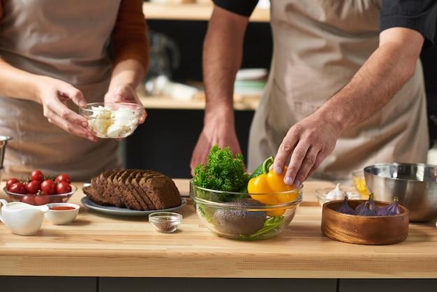 Gros plan, de, couple, dans, tabliers, prendre, ingrédients, et, préparer, nourriture, ensemble, table
