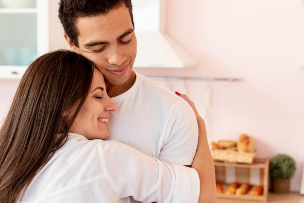 Gros plan, couple, étreindre, dans cuisine