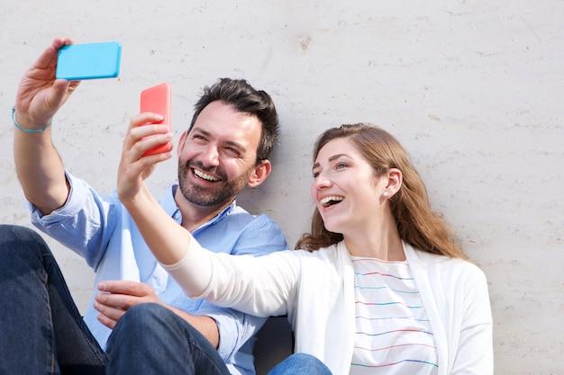 Gros plan d'un couple heureux tenant des téléphones cellulaires et prenant des selfies