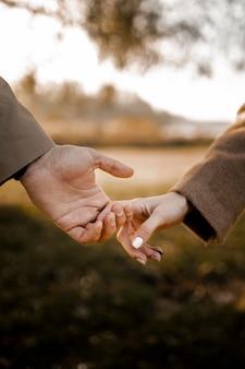 Gros plan couple main dans la main à l'extérieur