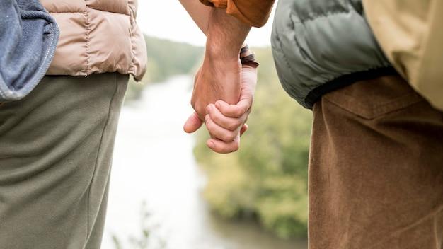Gros plan couple main dans la main près de la rivière