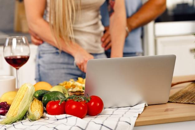 Gros plan d'un couple méconnaissable faisant cuire des aliments ensemble dans la cuisine