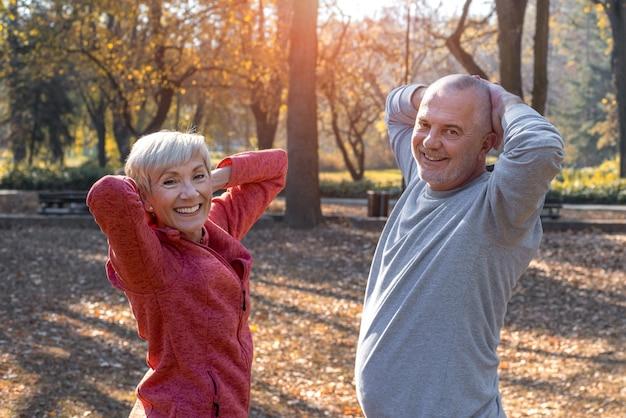 Gros plan sur un couple de personnes âgées caucasien souriant faisant de l'exercice dans un parc par une journée ensoleillée d'automne