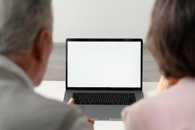 Gros plan sur un couple de personnes âgées avec un ordinateur portable