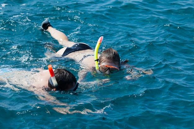 Gros plan sur couple plongée en apnée dans l'eau dans l'océan