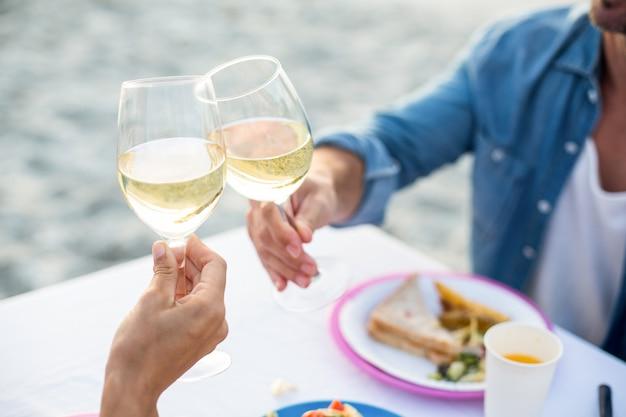 Gros plan d'un couple portant un toast au vin blanc