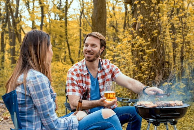 Gros plan d'un couple souriant faisant un barbecue dans la forêt
