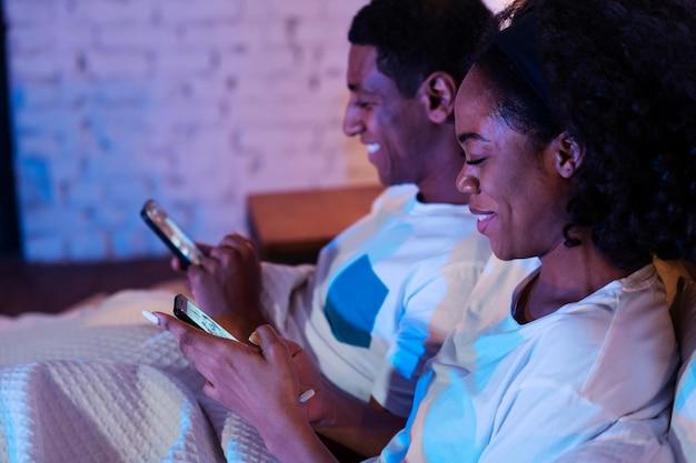 Gros plan sur un couple souriant avec des smartphones