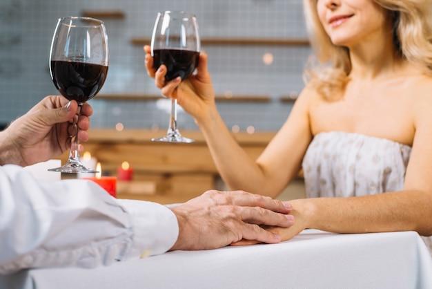 Gros plan, de, couple, tenant mains, à, dîner romantique