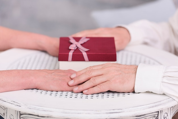 Gros plan, de, a, couple, tenant mains, près, boîte cadeau, sur, table