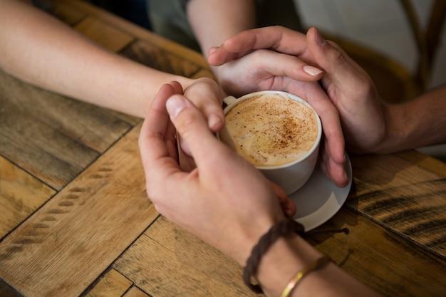 Gros plan, de, couple tenant mains, et, tasse café, dans, cafétéria