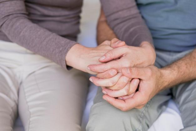 Gros plan, couples aînés, tenant mains