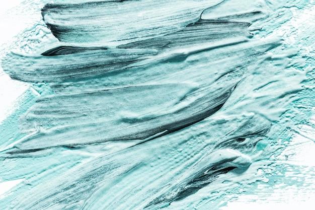 Gros plan des coups de pinceau de peinture bleue abstraite sur la surface