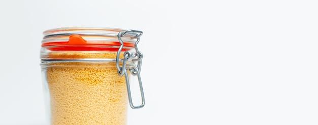 Gros plan de couscous cru dans un bocal en verre sur fond blanc avec espace de copie.