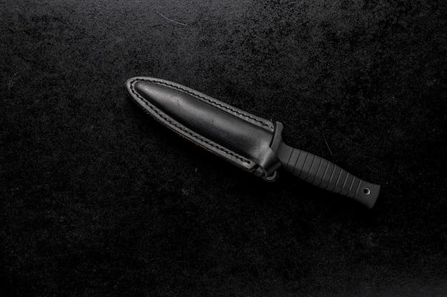 Gros plan d'un couteau tranchant fixe sur un fond noir