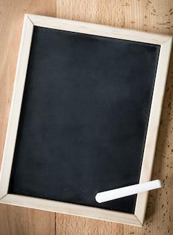 Gros plan sur une craie blanche allongée sur un tableau noir sur fond de bois