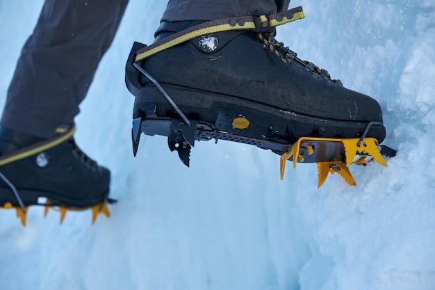 Gros plan des crampons sur ses pieds grimpeur sur glace, grimpeur sur un hiver gelé