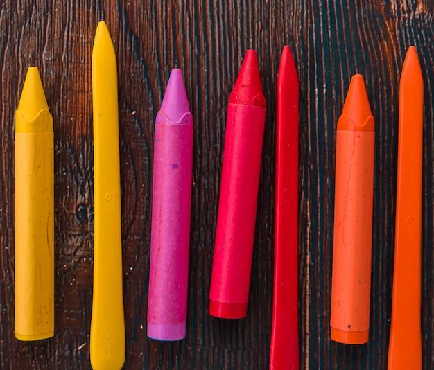 Gros plan de crayons de cire colorés sur une planche texturée en bois