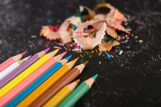 Gros plan avec des crayons de couleur et des copeaux sur sol en ciment, pose à plat.