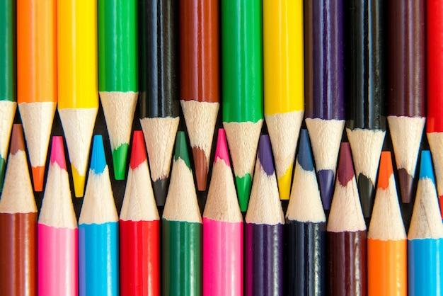 Gros plan de crayons de couleur disposés en motif imbriqué sur blanc