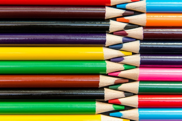 Gros plan de crayons de couleur disposés en motif imbriqué.