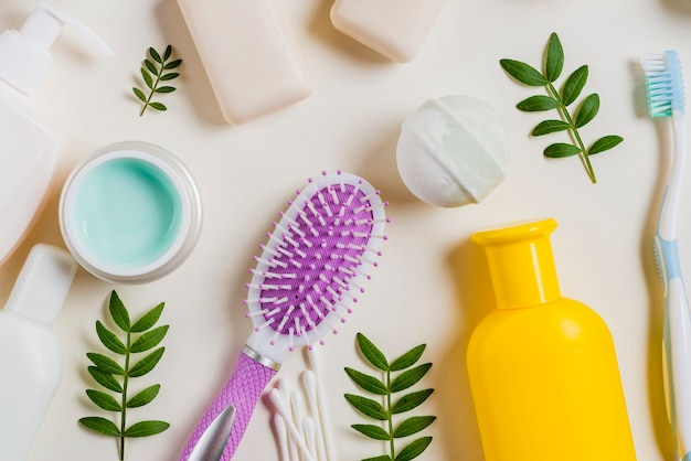 Gros plan de la crème; brosse à cheveux; savon; bombe de bain; brosse à dents sur fond blanc