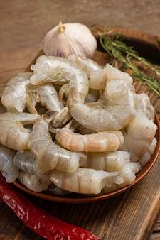 Gros plan de crevettes crues sur fond en bois.