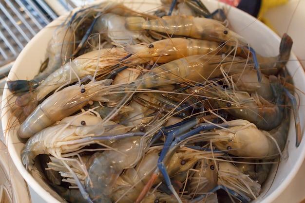 Gros plan des crevettes dans un bac en plastique avant la cuisson.