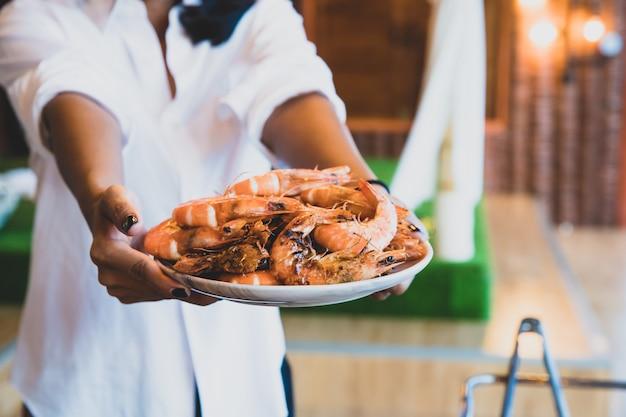 Gros plan de crevettes grillées sur le plat tenir par la femme de touriste. groupe de touristes ayant barbecue, fête de fruits de mer au bord de la mer.