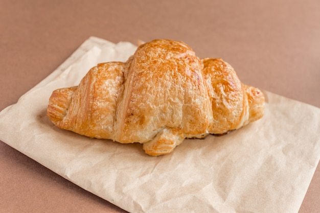 Gros plan d'un croissant français fraîchement sorti du four sur du papier kraft pour le petit déjeuner.