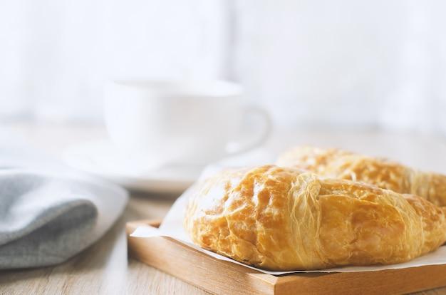 Gros plan d'un croissant avec une tasse de café sur une table en bois avec ton vintage