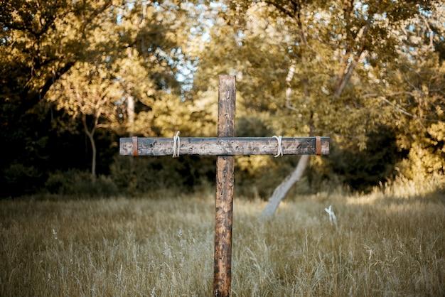 Gros plan d'une croix en bois dans un herbeux