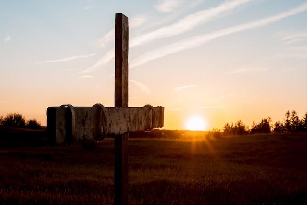 Gros plan d'une croix en bois à la main dans un champ herbeux avec le soleil qui brille en arrière-plan