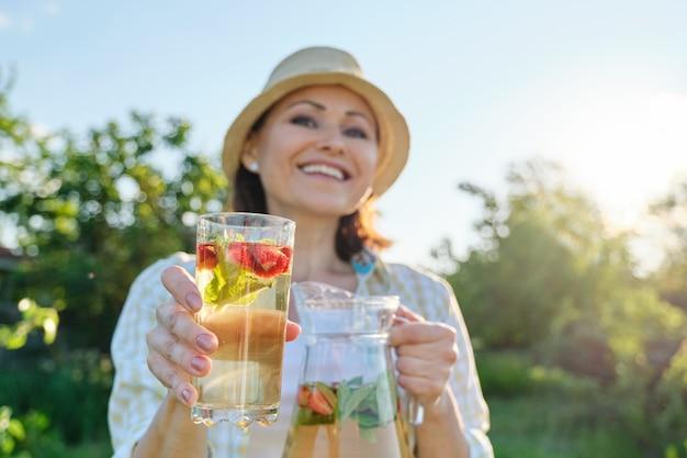 Gros plan de la cruche et du verre avec boisson fraise à la menthe aux herbes naturelles