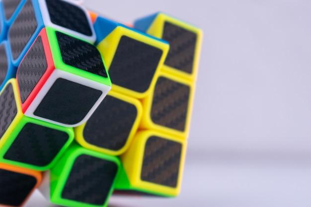 Gros plan d'un cube de rubik inachevé sur une surface blanche