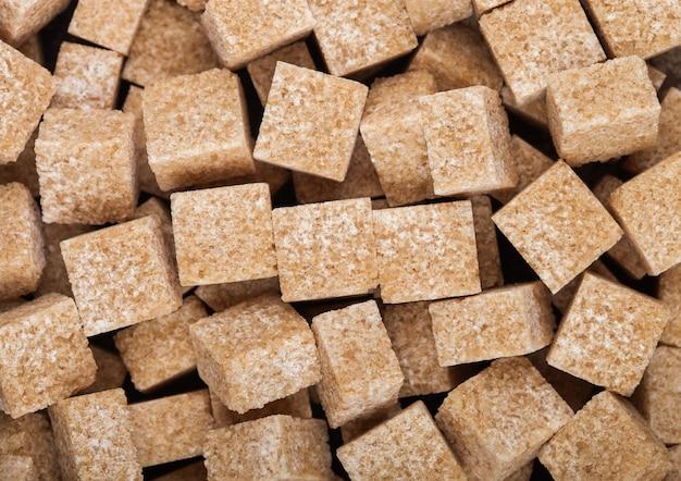 Gros plan de cubes de sucre brun naturel sur blanc. vue de dessus