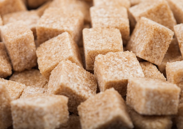 Gros plan de cubes de sucre brun naturel sur blanc.