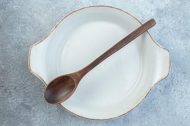 Gros plan d'une cuillère en bois dans une assiette à soupe blanche vide sur une surface gris clair à moitié foncée avec une surface en détresse avec un espace libre