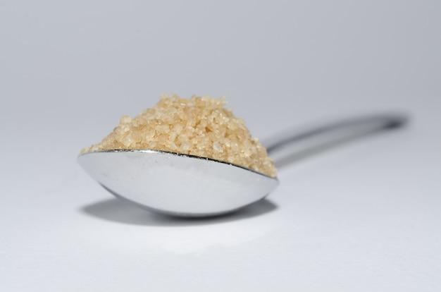Gros plan d'une cuillerée de sucre brun sur une surface blanche