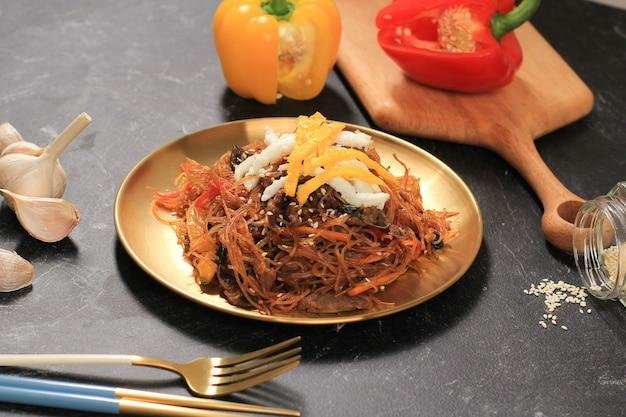 Gros plan sur une cuisine authentique coréenne, des nouilles japchae ou en verre sautées avec des légumes en plaque d'or. mangez tous les jours ou à chuseok day, copiez l'espace sur fond noir