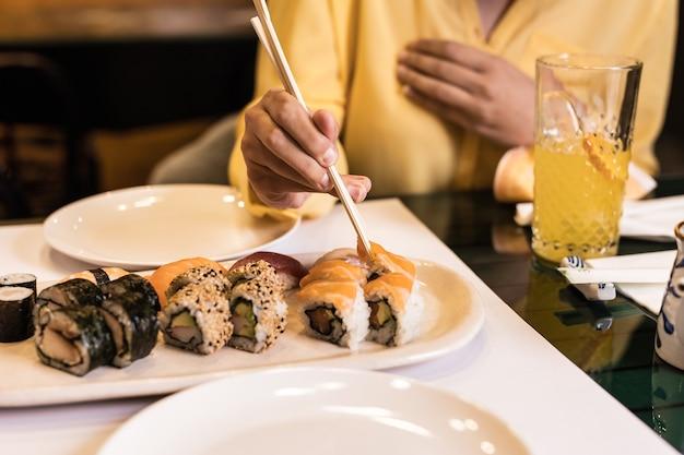 Gros plan de la cuisine japonaise de sushi avec la main d'une femme dans un restaurant sashimi de style de vie de délicieux fruits de mer et rouleaux de riz couleur jaune de l'année